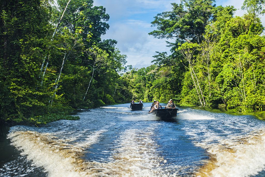 Two small boats sail down the Amazon river, on an excursion from Aqua Expeditions