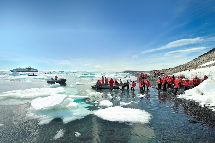 Zodiacs transporting people to shore excursions in Antarctica. Ponant ship can be seen in background.