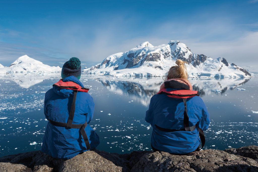 Two explorers sit side by side overlooking icy ocean and mountains