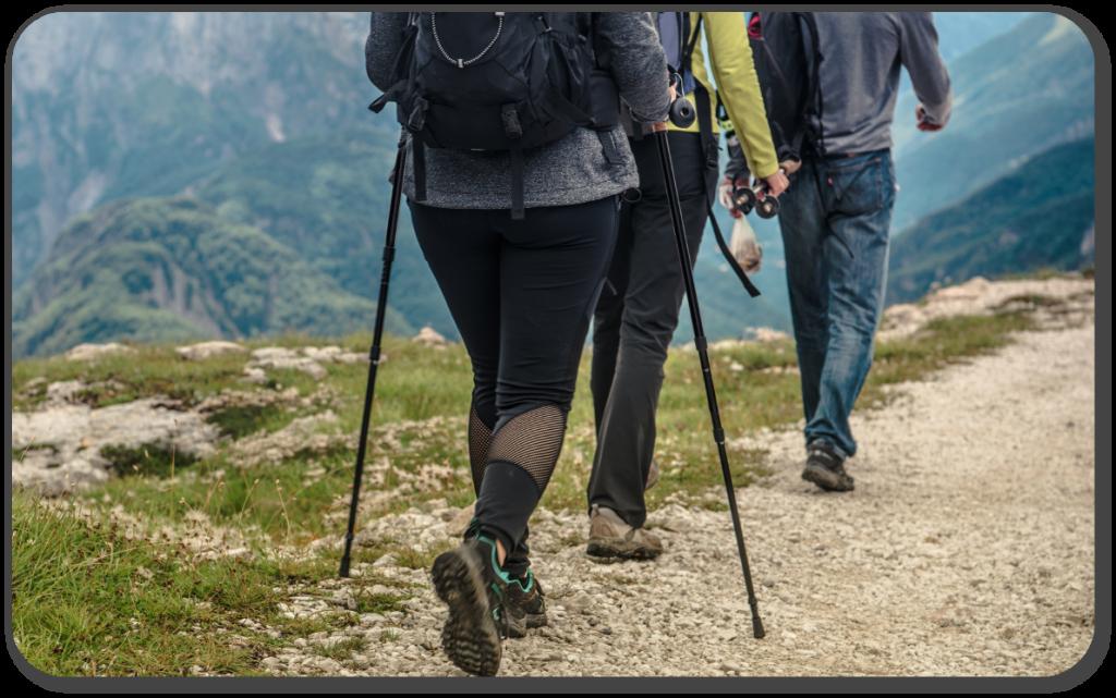 three people hiking with walking poles